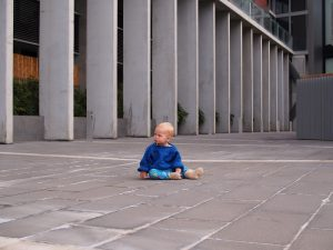 Young child about two and a half years old sitting on a featureless concrete yard at the base of a tower block