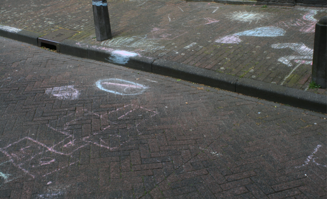 Chalk marks of children's play in public space. Hop scotch etc drawn on to the pavement and road.